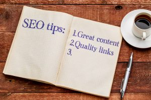 SEO (search engine optimization) tips (great content and quality links) in an old notebook with a cup of coffee